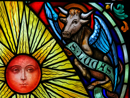 Stained Glass window depicting a Sun and a Bull, symbol of Saint Luke the Evangelist, in the Cathedral of Saint Rumbold in Mechelen, Belgium. Editorial