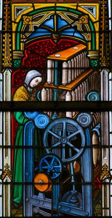 Gante, Bélgica - 23 DE DICIEMBRE DE, 2016: Vitral en la catedral de Gante, Bélgica, que representa a una fábrica de seda, una fábrica de prendas de seda que usan un proceso llamado de lanzamiento seda.