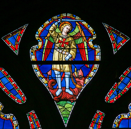 Stained Glass window depicting Saint Michael the Archangel slaying Satan, presented as a dragon, in the Cathedral of Saint Bavo in Ghent, Flanders, Belgium. Éditoriale