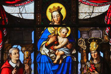 infant jesus: GHENT, BELGIUM - DECEMBER 23, 2016: Stained Glass (1851) in Saint Nicholas Church, Ghent, depicting Mother Mary and the Infant Jesus, Madonna and Child, and the donors and various saints.