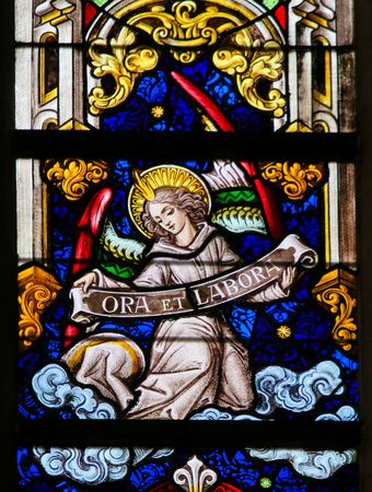 monastic: Stained Glass window depicting an Angel holding a sign Ora et Labore, the phrase pray and work refering to the Christian monastic practice of working and praying, in the Cathedral of Saint Bavo in Ghent, Flanders, Belgium.