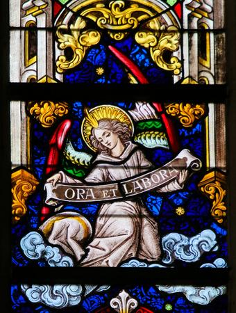 Vitrail représentant un Ange tenant une pancarte Ora et Labore, l'expression prière et travail se référant à la pratique monastique chrétienne de travailler et de prier, dans la cathédrale de Saint Bavo à Gand, en Flandre, en Belgique. Banque d'images - 69098234