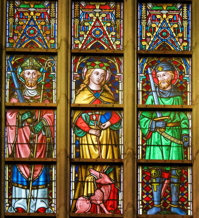 Stained Glass window depicting Saints Thomas, Margaret and Hermes in the Cathedral of Saint Bavo in Ghent, Flanders, Belgium. Editorial