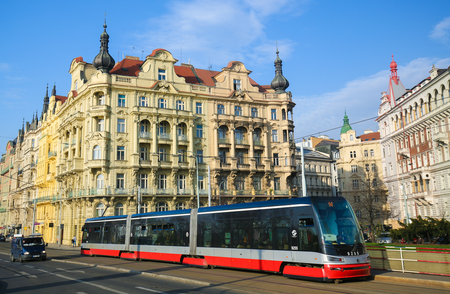 A typical red tram passing in front of the architecture of Nove Mesto or New Town in Prague, Czech Republic