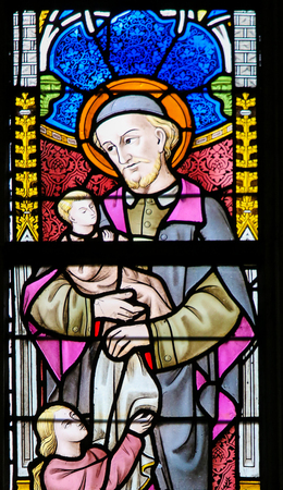 Stained Glass window depicting Saint Vincent de Paul in the Cathedral of Saint Bavo in Ghent, Flanders, Belgium.