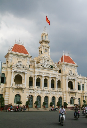 center hall colonial: Unidentified people passing in front of the City Hall building, Ho Chi Minh City, Vietnam. Editorial