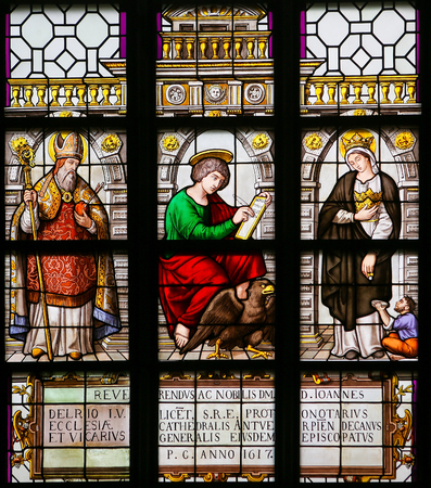 Stained Glass window in the 15th Century Elzenveld Chapel in Antwerp, Belgium, depicting Saint Augustine, John the Evangelist and Saint Elizabeth, Queen of Hungary, a symbol of Christian charity.