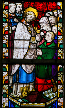 rite: Stained Glass window depicting a priest giving Holy Communion in the Cathedral of Saint Bavo in Ghent, Flanders, Belgium.