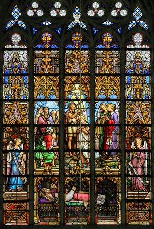 Stained Glass window in St Gummarus Church in Lier, Belgium, depicting the Baptism of Jesus in the River Jordan by Saint John the Baptist Editorial