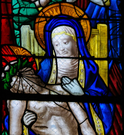Mother Mary mourning with Jesus who died on the Cross, on a stained glass in the cathedral of Rouen, France Stock Photo - 80846868
