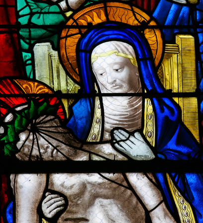 Mother Mary mourning with Jesus who died on the Cross, on a stained glass in the cathedral of Rouen, France