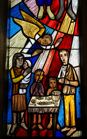 Stained Glass in the Stiftskirche Church in Tubingen, Baden-Wurttemberg, Germany, depicting a family gathered around a table, praying 에디토리얼