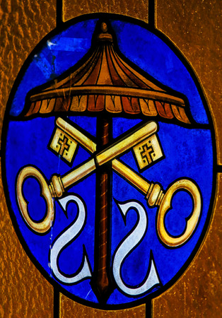 Stained Glass of the Umbraculum, and the Papal Regalia and Insignia in the Basilica of Santo Stefano in Bologna, Italy. Editorial