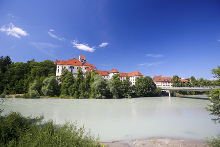 St Mangs Basilica and former monastery viewed from the bridge over the River Lech in Fussen, terminus of the Romantic Road in Bavaria.