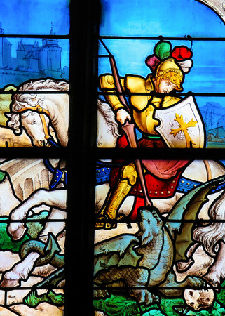 Saint George slaying the dragon on a Stained Glass window in the Church of Honfleur, France