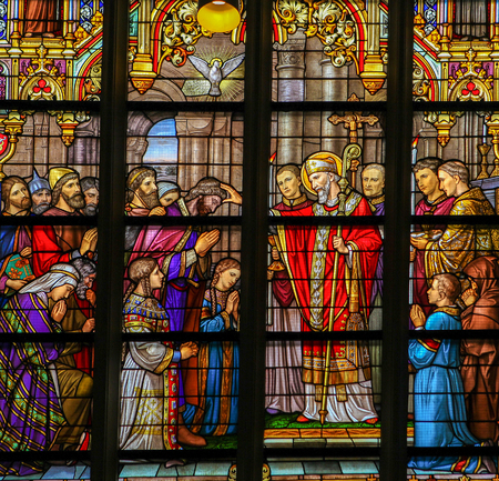 Stained Glass in Den Bosch Cathedral depicting Saint Lambertus anointing the Taxandrians during the Confirmation, the rite of initiation in the Catholic church. Editorial