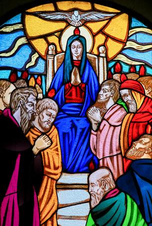 Glasraam met afbeelding van Moeder Maria en de discipelen van Christus met Pinksteren in de kerk van Ostuni, Apulië, Italië. Redactioneel