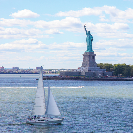 Sailing boat at the Statue of Liberty in New York City, US. Standard-Bild - 111812269