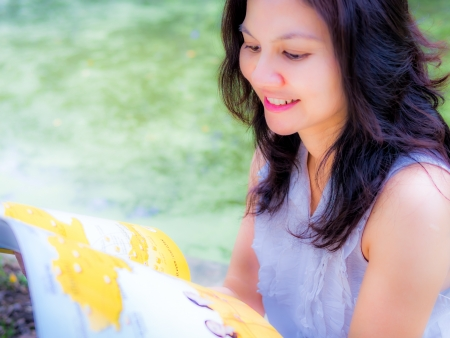Happy smiling woman reading a magazine   green background photo