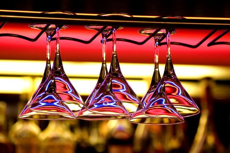 Glasses hang above a bar rack in cafe Stock Photo - 2100038