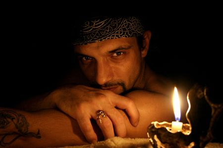 The man in an image of the pirate, near to it a candle