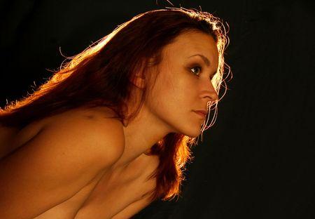 alight: Ritratto di giovane donna con i capelli rosso acceso su sfondo nero