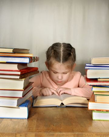 learning series: The little girl attentively read, many books on table near she Stock Photo