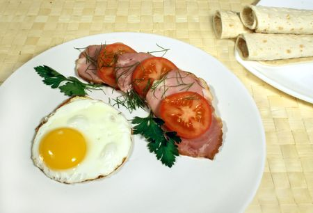 Fried egg (omelet) with ham and tomato photo