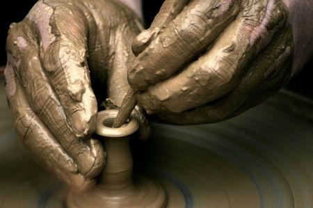 artisanale: Handen van de pottenbakker op pottenbakkersschijf, close-up