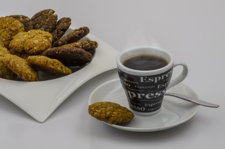 A Cup of Espresso Coffee and a Plate of Homemade HoneyChocolate and Oatmeal Cookies with White Copyspace. photo