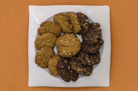 A Plate of Homemade HoneyChocolate and Oatmeal Cookies with Orange Copyspace. photo