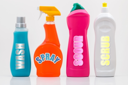 A Group of Colourful Household Cleaning Bottles with Labels on White. photo