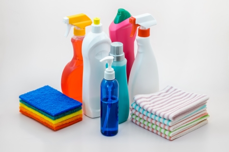 Group of Colourful Household Cleaning Bottles, Sprays, Pot Scourers, and Cleaning Cloths on White. photo