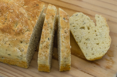 bread soda: Close Up view of a Loaf of Herb and Garlic Soda Bread, Sliced and presented on a Bread Board