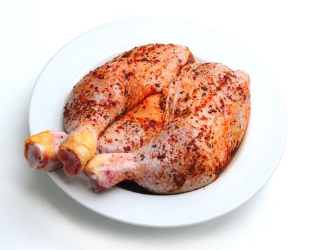 Spiced uncooked chicken legs in white plate photo
