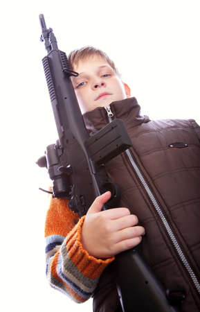 Child holding toy gun in hand against white background photo