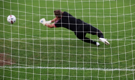 diving save: Soccer football goalkeeper making diving save