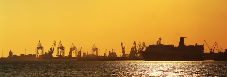 Harbor silhouette at sunset with ship and cranes photo