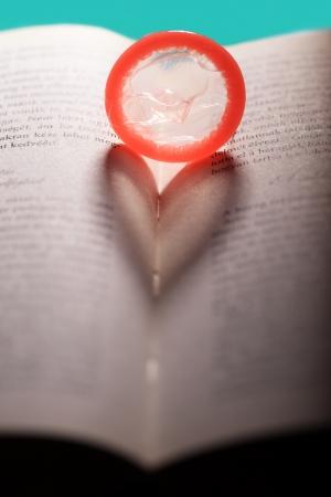 sexual education: Condón corazón rojo en el libro abierto Foto de archivo