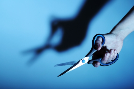 Scissors in hand on blue background with shadow photo