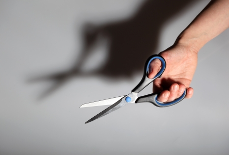 Scissors in hand on gray background with shadow photo