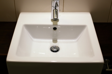 White modern ceramic handbasin and chrome tap photo