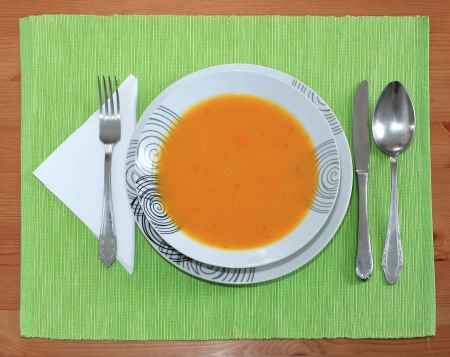 Pumpkin soup with cutlery on table photo