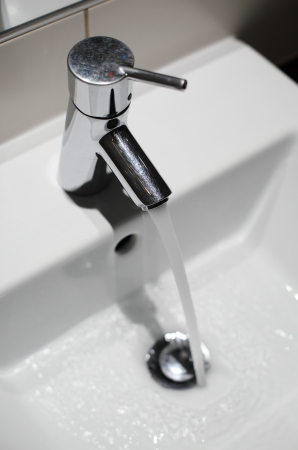Tap with running water in bathroom photo
