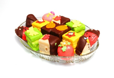 Various colorful marzipan cakes on glass plate photo
