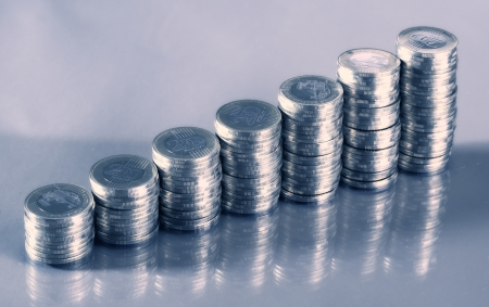 dosh: Seven coin piles with reflection Stock Photo
