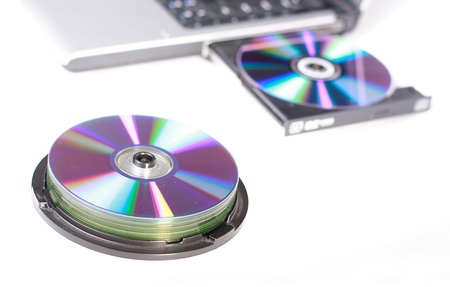 dvdrw: Laptop with dvd drive open and loaded and a pile of dvd