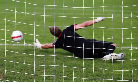 diving save: Soccer football goalkeeper making diving save
