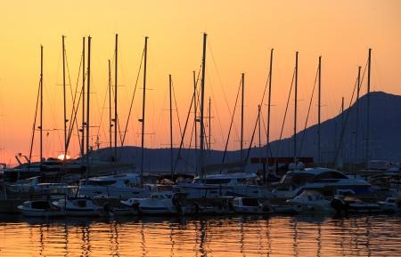 Sailing boats in marina at sunset photo
