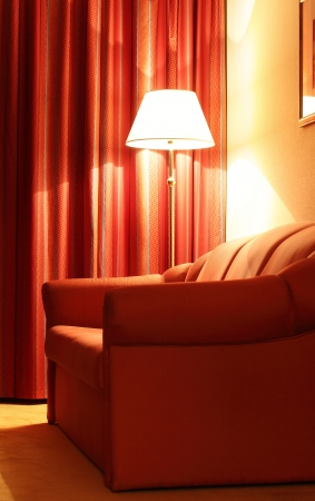 Hotel interior with red couch and floor lamp photo